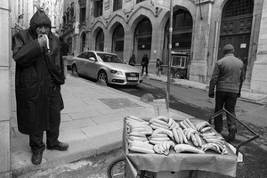 A banana vendor eats one of his bananas as he waits to make a sale.