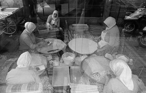 Women seen through a restaurant window, make Gozleme, thin layers of dough filled with cheese, meat or vegetables and toasted on a convex grill.
