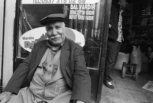 A shopkeeper sits in front of his shop.