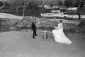 A newly-wed couple pose for photographs while sitting on a child's see-saw in the partially built Macka Park.