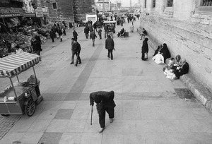 An elderly man walks with the aid of a stick past the Yeni Cami (New Mosque).