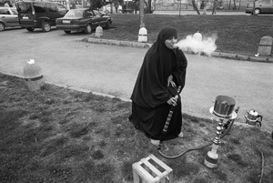 A woman dressed in a chador exhales smoke from a hookah (narghile, sheesha) as she sits in a park in Fener.