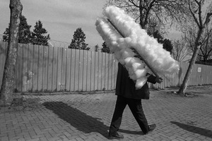 A man selling candy floss walks along a street.