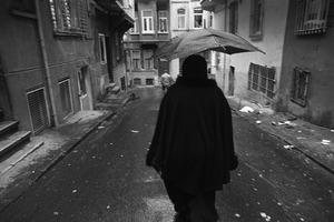 A woman shelters from the rain beneath an umbrella as she walks along a narrow street.
