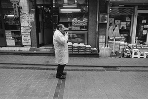 A shopkeeper drinks a glass of tea in while standing in front of his shop.
