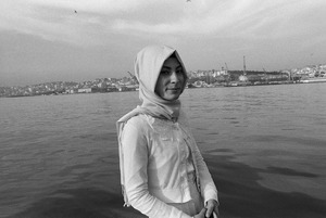 A young woman, dressed in white, stands on the shore of the Golden Horn (Halic in Turkish).