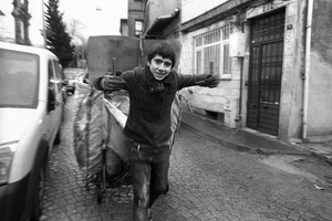 A young man pulls a trolley loaded with cardboard for recycling along on of the city's cobbled streets.