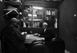 A man stands outside a tea shop and smokes while watching a group playing cards inside.