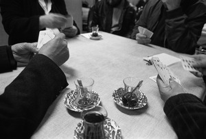 A group of Kurdish men drink tea and play cards in a tea shop.