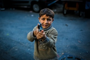 "A small kid is playing ""war-war"" with a toy gun on the street. © Turjoy Chowdhury"