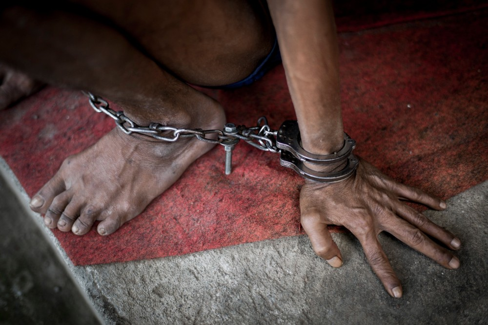 Indonesia, Bali, Singaraja. April 16, 2013. A chained man in the jungle in Singaraja. © Christian Werner