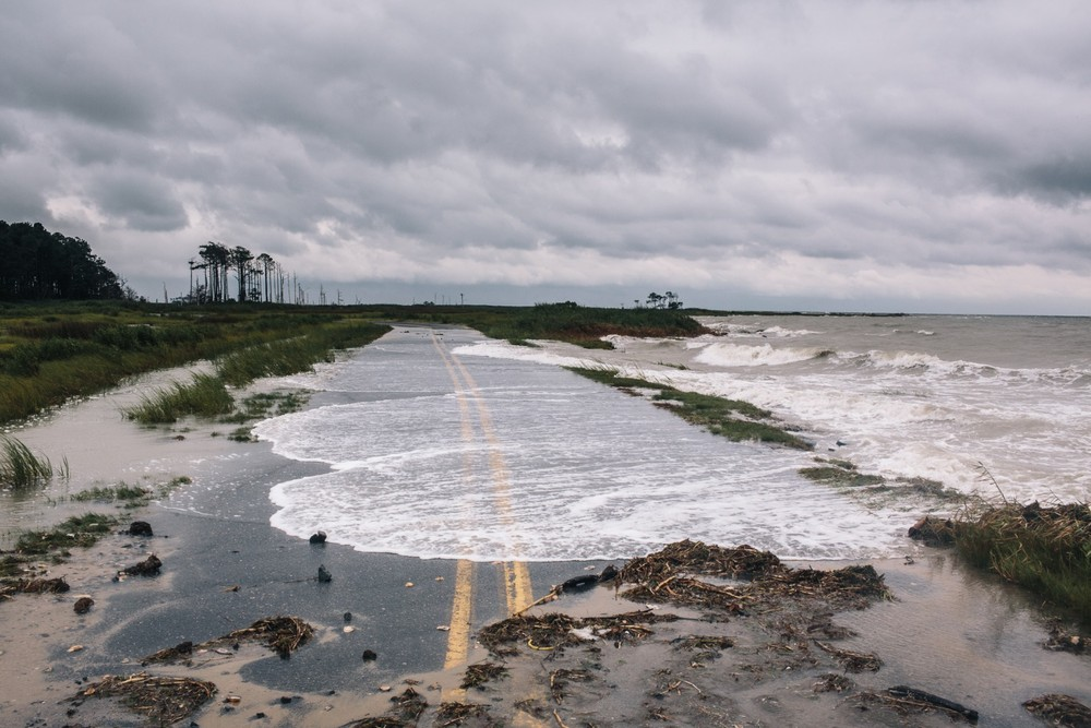 High Tide. Water spills onto Hoopers Island Road, up the coast from Crisfield. The bay is a foot deeper than it was at the start of the 20th century, meaning that storm surges are higher and that land in the region is sinking. © Greg Kahn