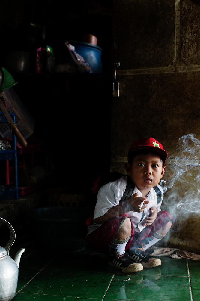 Dihan Muhamad used to smoke up to two packs of cigarettes a day before cutting down. Still, he must have his first cigarette at 7 AM before attending his first grade classes. Village, near the town of Garut in West Java, Indonesia. © Michelle Siu