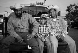 Thad, Tyler, and Thaddeus Heard are three generations of cowboys. Thad, a retired fireman, has been riding in the rodeo since 1994 in the steer wrestling competition. Thaddeus is a cook at Waffle House and plans to start competing in the rodeo when Tyler is a little older. They were photographed at the Bill Pickett Rodeo in Atlanta, GA on August 2 & 3, 2014. © Forest McMullin