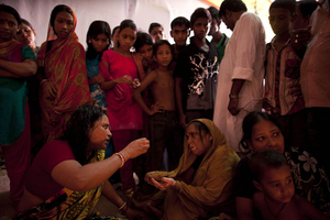 On the last day of Durga Puja, this woman dispenses advice to other worshippers. She sat in the priest's place, barking orders at everyone, even the Brahmins, who seemed to obey her without question. Her eyes were wide open, showing white all the way around her pupils; the furiousness of her trance-like stare was heightened by the somber, deep tone of her voice. Some brought children in need of healing, whom she would grab with her thick, strong arms and rock violently back and forth. © Claudio Cambon
