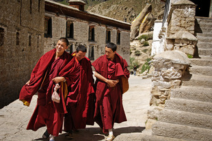 These monks are on their way to attend noontime devotions in the main temple at Drepung Monastery. Drepung sits high on a mountainside outside of Lhasa, Tibet. It was once the largest monastery in the world with 10,000 monks in residence. Today, about 700 live there. Photographed on 29 June 2005 © Forest McMullin