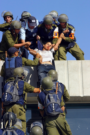 Homesh, Aug 05 - Israeli soldiers carefully lower dehydrated Jewish settler from barricaded rooftop © Natan Dvir