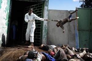 1st Prize General News Stories © Olivier Laban-Mattei, France, Agence France-Presse. Haiti earthquake aftermath, 15-26 January A man throws a dead body at the morgue of the general hospital, Port-au-Prince, 15 January