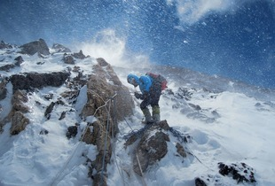 Buffeted by stinging blasts of wind-driven snow, Gerlinde Kaltenbrunner checks the ropes the team has spent weeks fixing along the entire route—9,000 feet of rope in all. From the October 125th anniversary issue of National Geographic magazine © Ralf Dujmovits/National Geographic