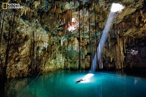 A single frame can transport us to one of our planet's far-flung and beautiful places. In this one, stalactites and a sunbeam spotlight a swimmer in the Xkeken cenote, a natural well in the Yucatán thought by the Maya to lead to the underworld. From the October 125th anniversary issue of National Geographic magazine © John Stanmeyer/National Geographic
