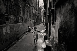 A girl skipping in a narrow alley. Modon Shaha Lane, 2006. © Munem Wasif