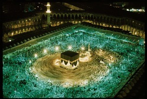 "Pilgrims circle the Kaaba in Mecca, Saudi Arabia.  Making this time exposure from the roof of his nearby hotel, Abercrombie watched the faithful, dressed anonymously in white, circle the Kaaba ""in harmony with the planets and the atoms,"" he wrote. Saudi Arabia, 1965 © Thomas J. Abercrombie, National Geographic"
