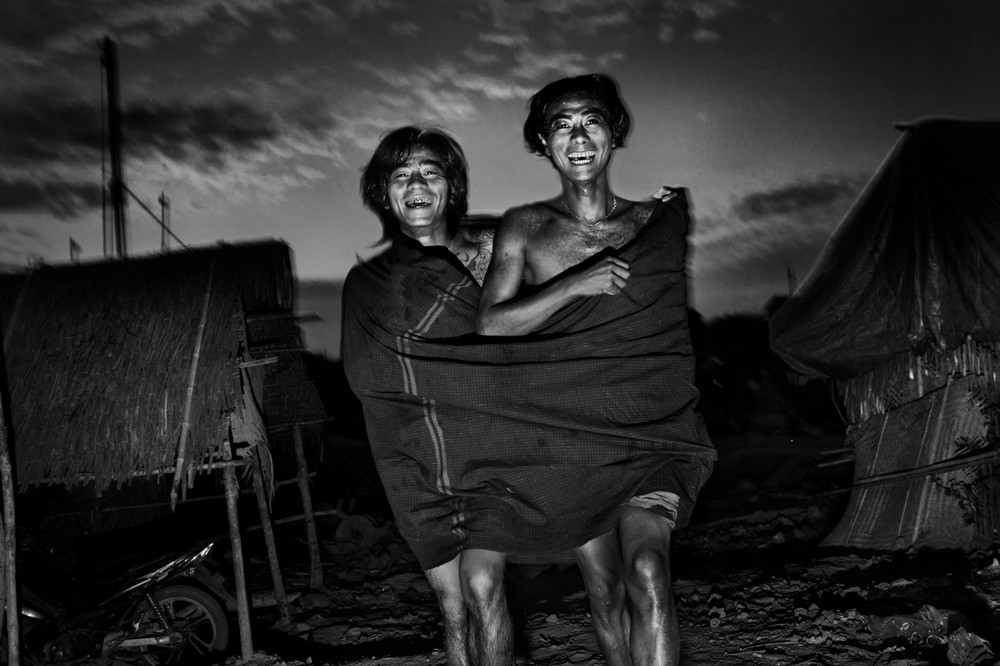 Kyaw Swar and his friend have a laugh while returning to their tent after an evening bath. Htankhi, magway Division, Myanmar