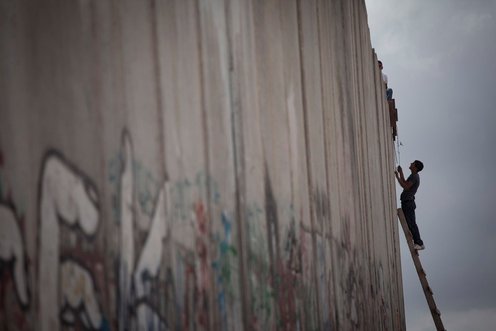 A Palestinian boy climbs to the top of the Separation Wall near Qalandiya checkpoint, 2011