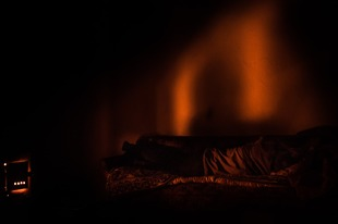 Man warming himself near the furnace. Ptsirtskha village, Abkhazia. © Olga Ingurazova