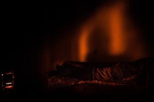 Man warming himself near the furnace. Ptsirtskha village, Abkhazia. © Olga Ingurazova