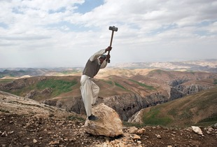 © Iva Zimova.  A labourer uses a sledgehammer to break a large rock into pieces during the construction of a road that connects the villages of Shakardara and Kujara.