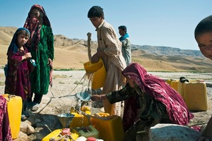© Iva Zimova. A group of women and children collect water from a well beside the road from Zare to Marghzar.