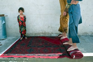 © Iva Zimova. A young girl watches on as men use their feet to wring out a carpet that they washed on the street.