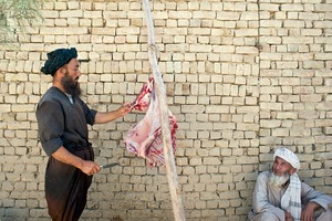 © Iva Zimova. A butcher cuts peace of goat in a shop on the street of Mazar-e Sharif.