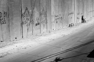 The Palestinian community of East Jerusalem is separated from the rest of the West Bank by 36-foot tall concrete blocks. The Wall roughly runs along the East Jerusalem municipal district border and not the 1967 Armistice Line. Covering much of the Wall is graffiti that is usually critical of the Israeli government as well as America and the Bush Administration. © Morgan Hagar