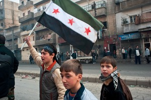 © Iva Zimova. Aleppo. A boy carries the Syrian flag used by the rebel movement in a small demonstration after Friday prayers in the street in the Alfardous district in Aleppo.