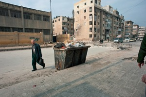 © Iva Zimova. Aleppo. A man walks past a garbage container in the Bustan Al Qassar district. On houses behind him and on the street, evidence of recent fighting is visible. The street is mostly deserted due to the danger of sniper fire.