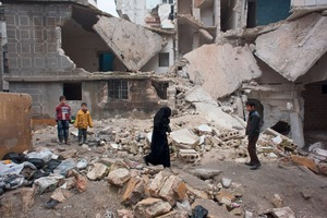 © Iva Zimova . A woman walks by the remains of the Al Waleed School in Alfardous district in Aleppo.