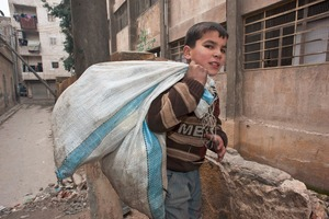 © Iva Zimova. Aleppo. A boy carries a bag containing plastic bottles he has found on the streets.