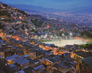 The Granizal district of Medellin, Colombia, first populated by refugees (IDPs) 30 years ago. The football pitch was previously the camp's refuse patch and can't be built on due to the danger of subsidence. © Simon Norfolk