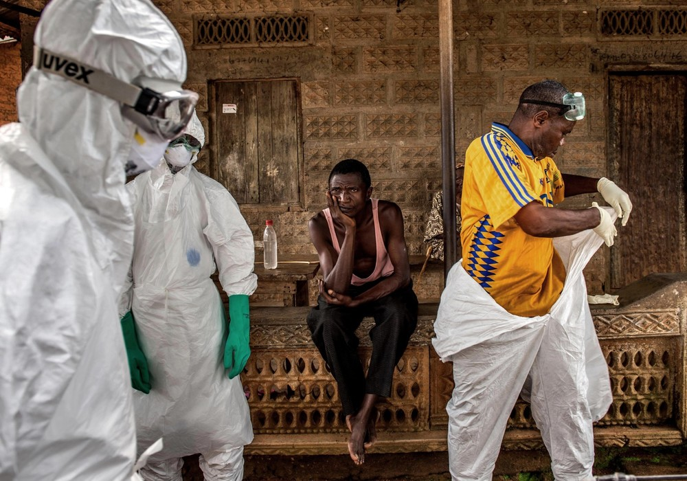 A man looks on as members of a burial team prepare to collect the body of his next door neighbor who is thought to have died from the virus.