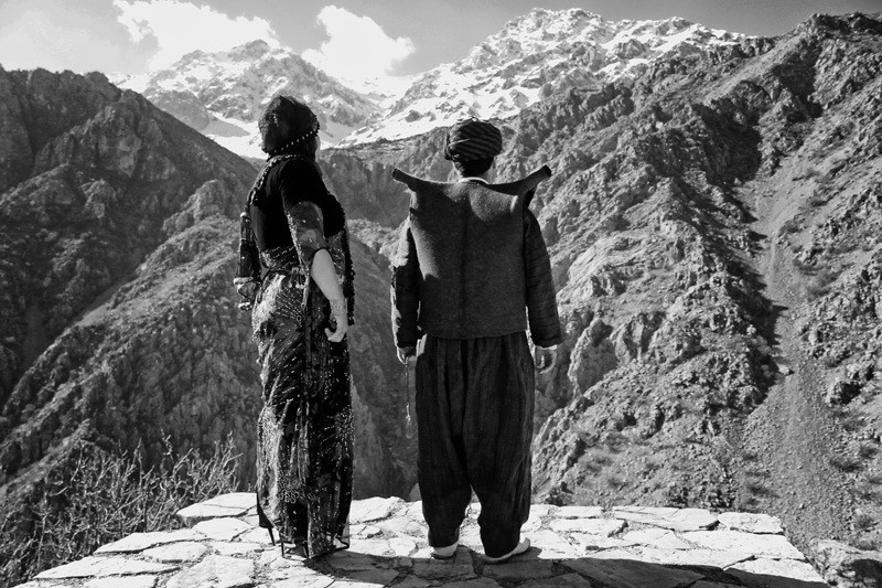 A Hawrami couple with their traditional dress stands on the edge of cliffs and look at the Shahu mountains.