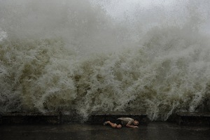 A boy is hiding from a big wave on the Black Sea embankment during a storm in Sochi.