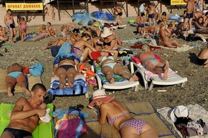 Tourists take sunbath on the beach of Sochi near the Black sea.