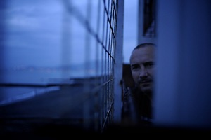 Alexey Kravets is looking through a barbed wire fence.In October 2012 officials executed a court order and demolished Alexei Kravets' house at 65 Prosvesheniya Street in the Adler section of Sochi. Kravets did not let them in until local Child Protection Services officials arrived, as his thirteen-year-old son was at home.Officials forced their way into the house and threw the family's furniture,