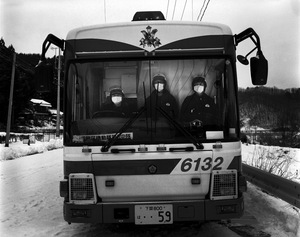 """Three police officers at the checkpoint of Tsushima district, 27 km from Fukushima. Normally the exclusion zone is set at 20km, however, due to high level of radiation here, 4-9 micro sv/h, they set the checkpoint further. At most checkpoints, the officers deployed are relatively young, ready for work despite the high level of radiation. From the series """"Fragments/Fukushima"""" © Kosuke Okahara"""