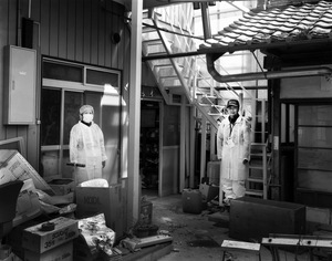 "Takami and Noriko Ohara came to check their abandoned house in the exclusion zone. They used to run a small local shop. Their old home is damaged as it has been empty for over two years. They would like to come back to live but they are not optimistic. Tomioka town, Fukushima prefecture. From the series ""Fragments/Fukushima"" © Kosuke Okahara"