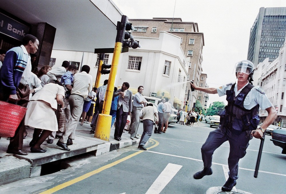 A policeman tear-gassing a crowd that had spontaneously congregated in the streets of central Johannesburg to celebrate the announcement of the unbanning of political parties, including the ANC and Pan-African Congress, 1990 © Graeme Williams