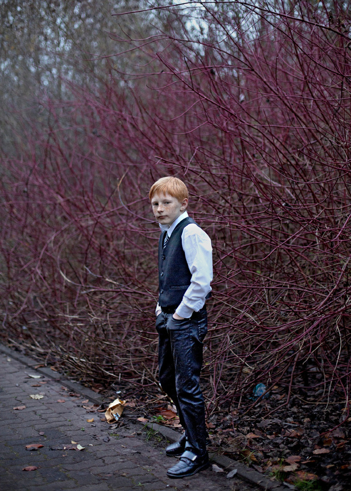 A red head boy poses in his Sunday clothes. Germany, 2015