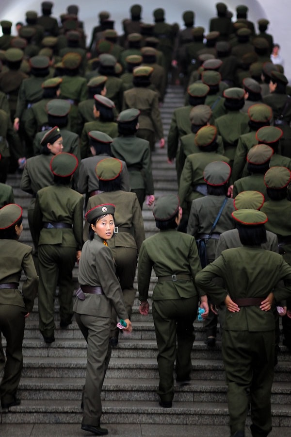 A female soldier looking back into the camera in the subway of Pyongyang.